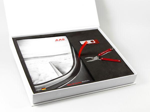 Geschenkverpackung für Firmengeschenke und Booklet - Mit zugeschnittenem Einleger aus Schaumstoff und einem roten Textilbändchen, passend zur CI der Firma