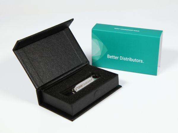 Kleine USB-Stick Verpackung in einem Standardformat mit Inlay aus Schaumstoff und einer vollflächig bedruckten Banderole als optische Aufwertung der Box.