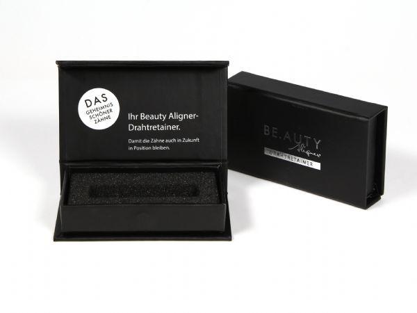 Kleinformatige Klappschachtel in der Größe 85 x 48 x 14 mm (Innenmaß) mit Logo für einen Drathretainer. Mit Schaumstoffinlay für das Produkt zur Zahnkorrektur.