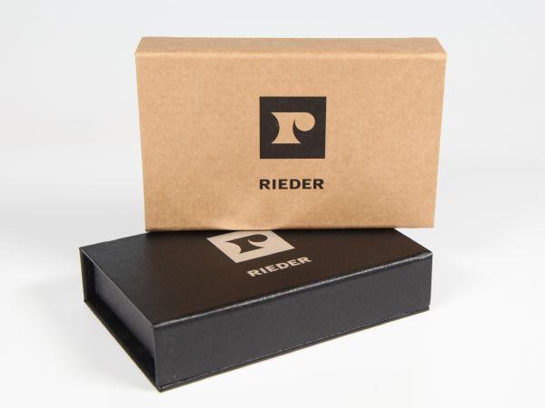 Verpackung mit verschiedenen Oberflächen. Einmal mit Reclyclingpapier und einfarbigem Logodruck und einmal mit strukturiertem Papier und Silberprägung
