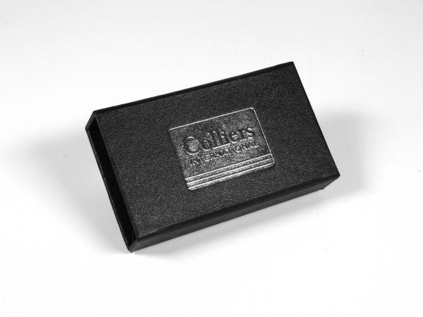 Eine Klassische, kleine Verpackung in Standardgröße für USB-Sticks und Dongles mit strukturierter Oberfläche und Heißfolienprägung in silberner Farbe.