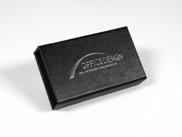 Standardbox für USB-Sticks bzw. Dongles in kleinem Format mit strukturierter Oberfläche und edler Silberprägung des Logos auf der Oberseite des Klappdeckels.
