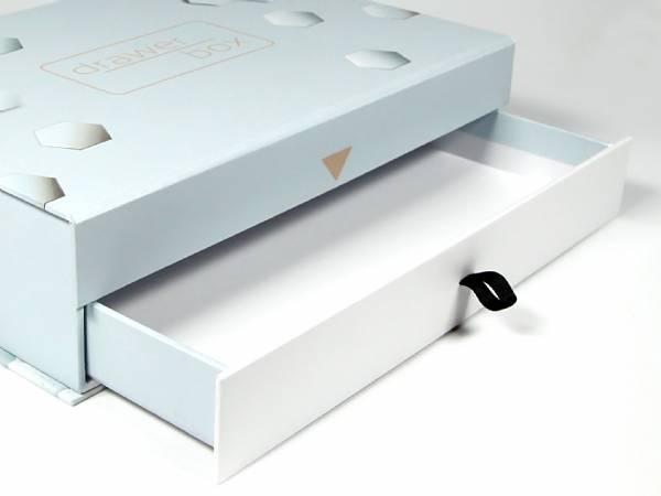 Schubladenfach der Drawer Box aus Vollkarton. Mithilfe eines Textilbandes kann diese herausgezogen werden. Optional mit einem Inlay aus Schaumstoff ausstattbar.
