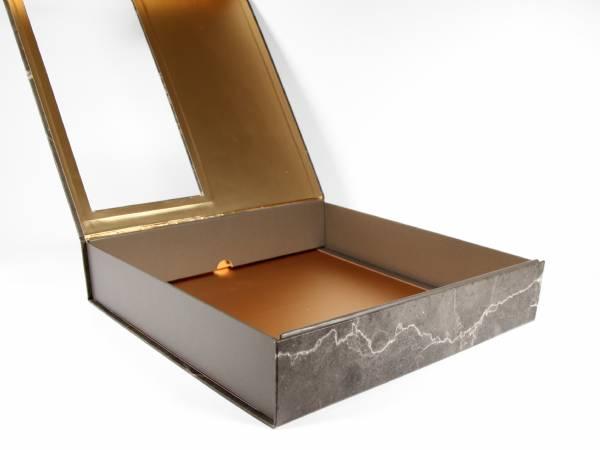 Selbstaufrichtende Magnetschachtel mit Magnethalterung im Deckel zum sicheren Verschließen. Vollflächig bedruckbar. Goldveredelung. Schachtel mit Sichtfenster.