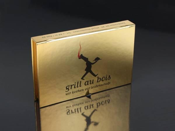 Verpackung in Buchform mit Magnetschluss, vollflächig mit goldenem Papier mit farbiger Bedruckung. Ein Aufdruck ist an allen sichtbaren Seiten möglich.