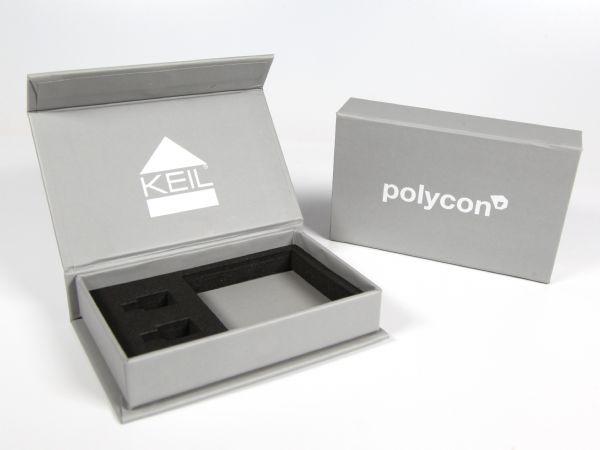 Hochwertige aber schlichte graue Magnetklappschachtel mit Aufdruck des Firmenlogos in Weiß. Mit Inlay aus festem Schaumstoff mit Ausstanzungen nach Wunsch.