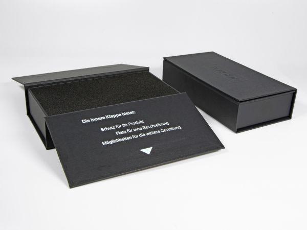 Die Flap Box mit bedruckter Innenseite auf einer Klappe - Mit Hoch- und Tiefenprägung des Logos auf den Oberseiten - Mit einem Inlay aus weichem Schaumstoff.