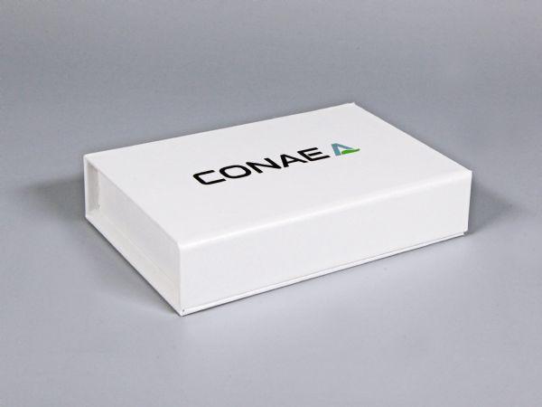 Schlichte Produktverpackung für Industriekunden- Magnetklappbox in mattem Weiß mit zweifarbigen Aufdruck des Firmenlogos auf der Oberseite der Verpackung.