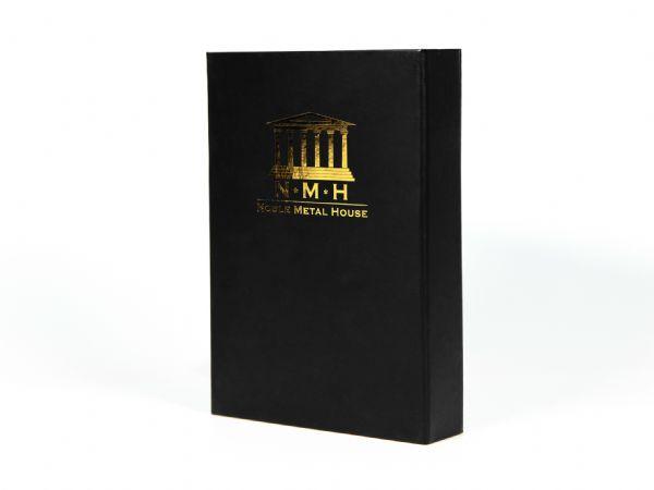 Eine edle, matte Geschenkbox in Schwarz mit einer goldenen Heißfolienprägung, die das Logo des Edelmetallshops auf der Vorderseite hochwertig hervorhebt.