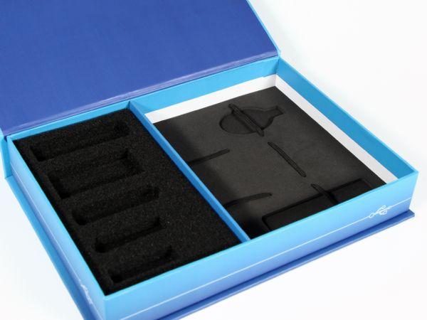 Mit Trennsteg aufgeteilte Box mit Schaumstoffinlay in schwarz mit verschiedenen Aussparungen