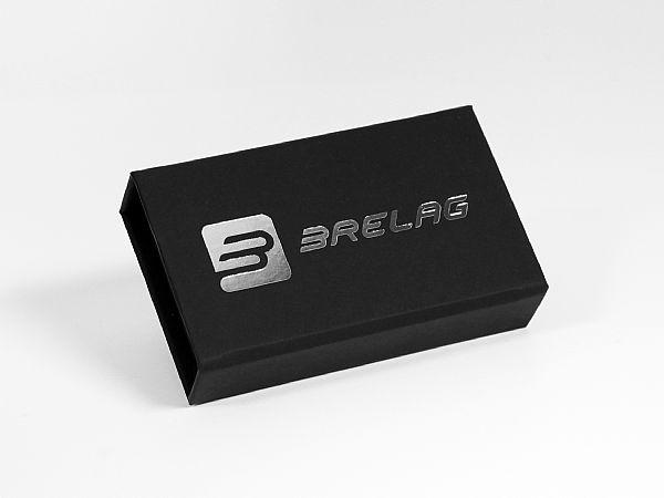 Eine schwarze Klappbox mit Softtouch Oberfläche und einem edlen silbernen Heißfolienprägedruck. Als Inlay dient ein passend geschnittener Schaumstoff.