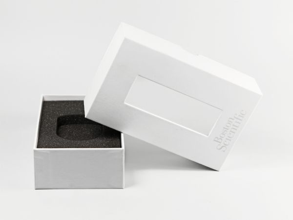 Box mit Stülpdeckel und Sichtfenster. Einfarbiges Logo auf dem Deckel und Schaumstoff als Inlay im Inneren..