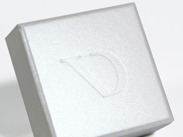 Kleine Box mit Stülpdeckel in weißem Strukturpapier und dezentem Logo als Blindprägung. Innenmaße der Box 60 x 60 x 21 mm mit schwarzem Inlay aus Schaumstoff