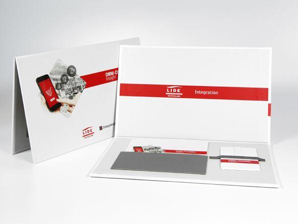 Die ultraflache Verpackung für eine USB-Karte und einen Flyer ist eine Pressemappe mit Magnetverschluss. Eine andere Aufteilung in der Mappe ist möglich.