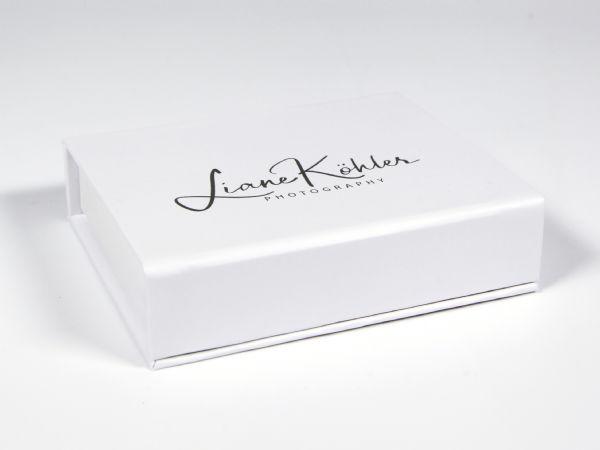 Weiße Klappschachel mit schlichtem Logoaufdruck und rosa Inlay für USB-Stick (klick!)
